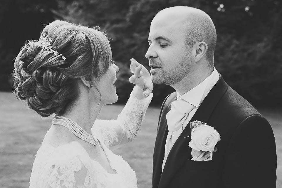 Bride wipes lipstick off the groom in the gardens at Bath Spa Hotel
