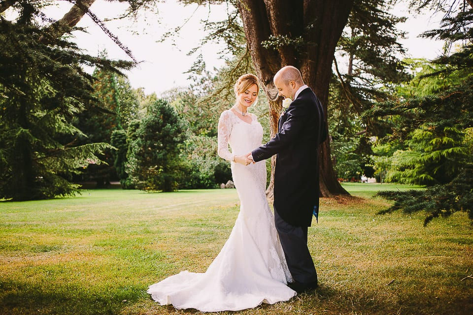 Portrait of the bride and groom under a tree in the gardens at Bath Spa Hotel