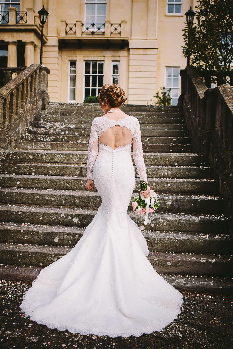 Bride walking up the steps in the garden