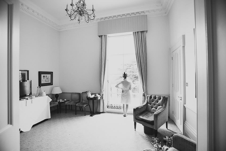 Black and white image of bride looking out of the window at Bath Spa Hotel