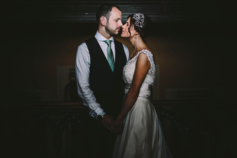 Close portrait of the bride and groom on the grand staircase of Grittleton House