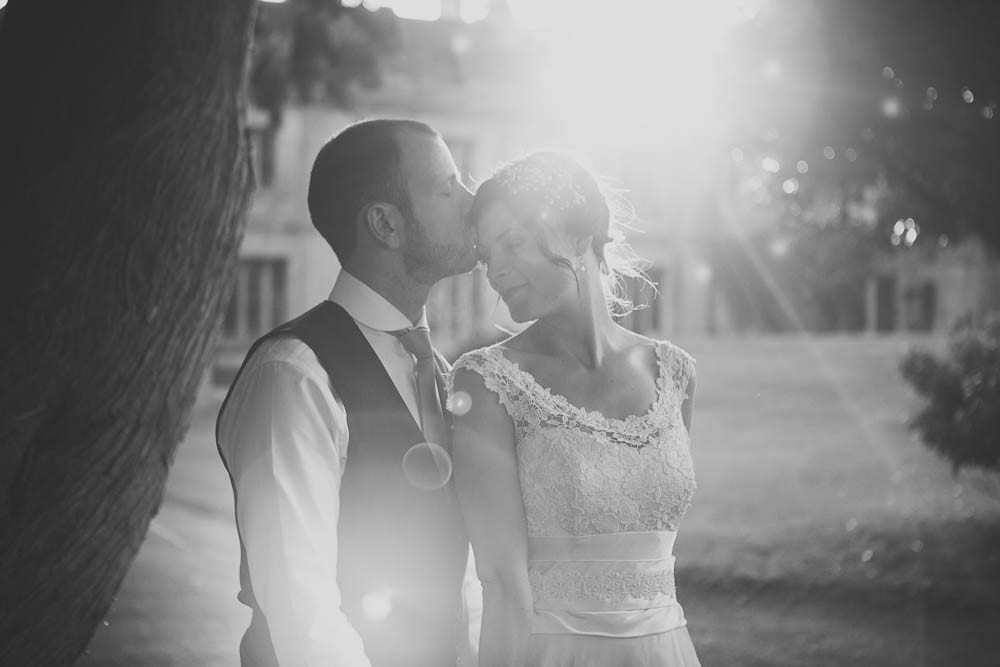 Black and white image of groom kissing brides forehead in the gardens