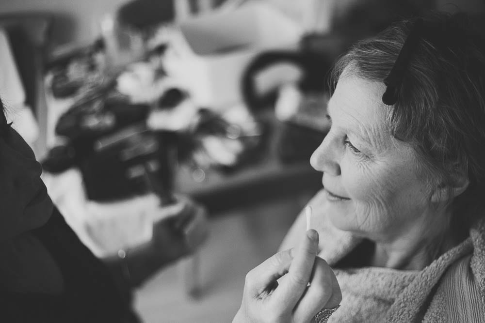 Black and white image of mother of the bride having her make up done