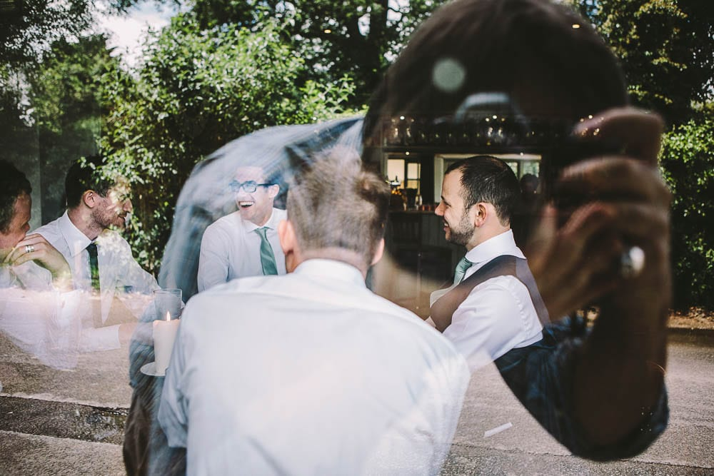 View of the groom and his groomsmen through the window of the Somerford Arms