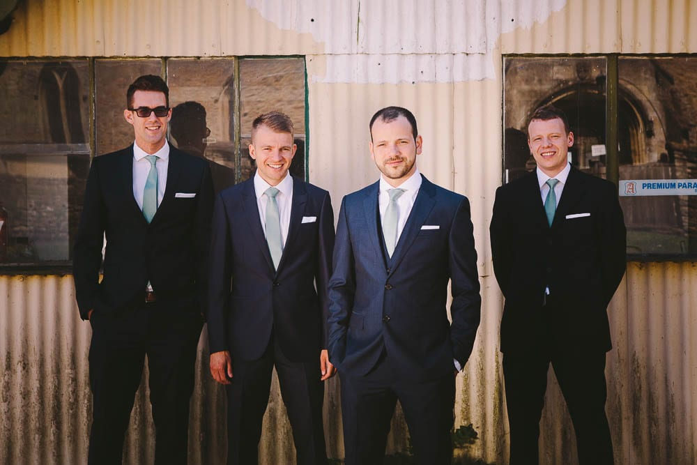 Groom and his groomsmen outside disused garage in Little Somerford