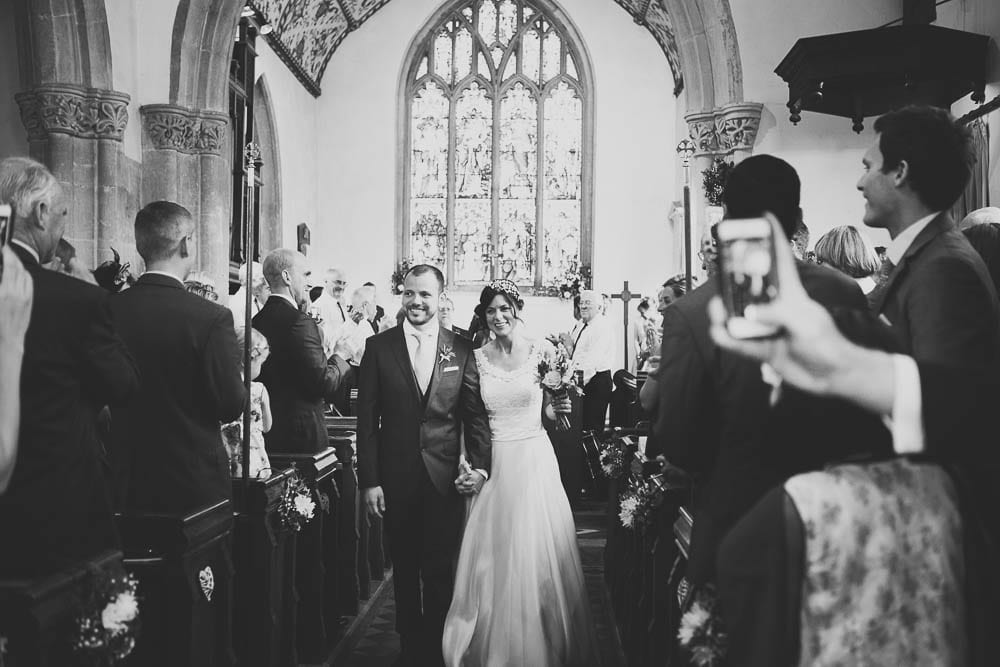 Black and white image of bride and groom exiting Great Somerford church