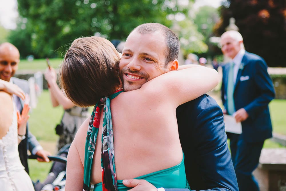 Groom being hugged by a guest at Great Somerford church