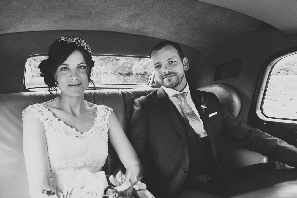 Black and white image of bride and groom in the wedding car