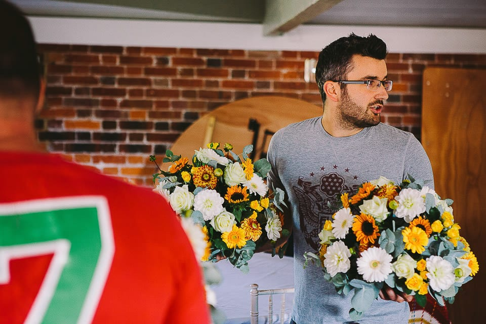 Groomsman carrying table decorations for the wedding breakfast at Sopley Mill