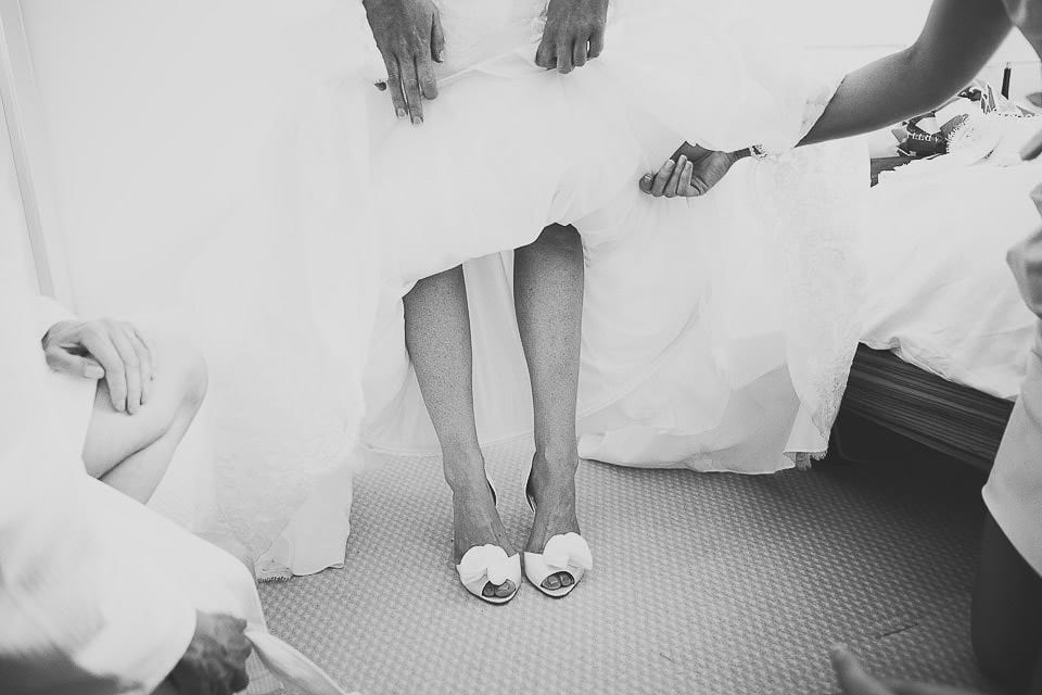 Black and white image of bride showing her shoes at The Captains Club Hotel
