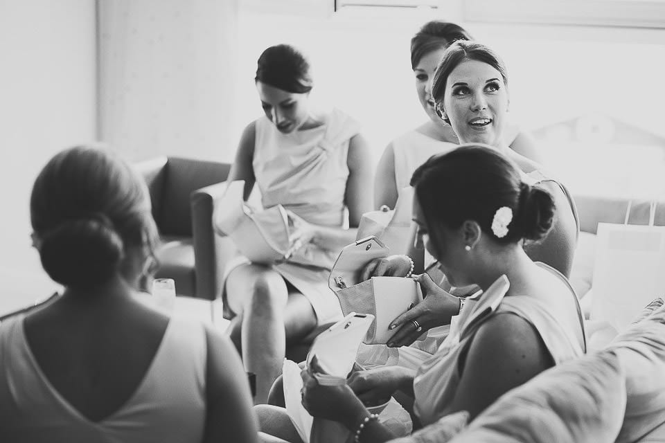 Black and white image of bridesmaids opening their presents from bride at The Captains Club Hotel