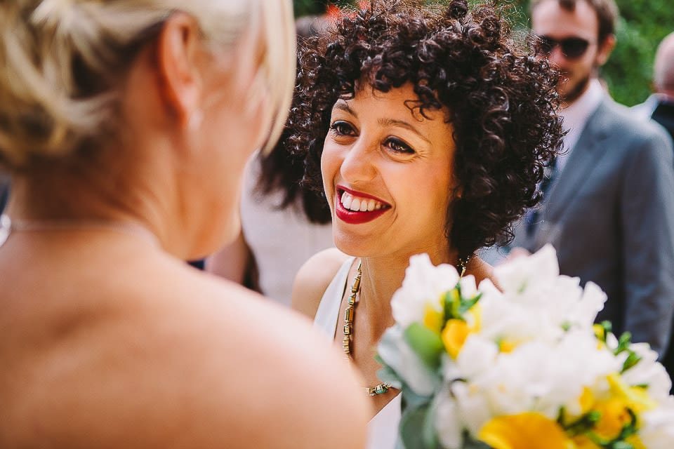 Bride chatting to a friend in the gardens at Sopley Mill