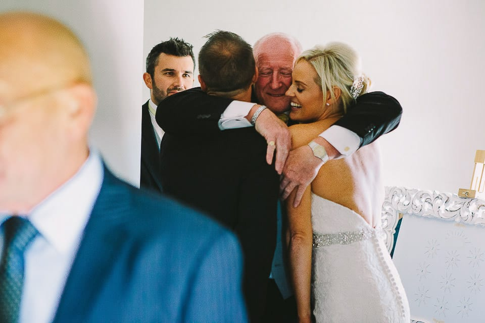 Bride and groom getting a hug from her grandfather in the receiving line at Sopley Mill