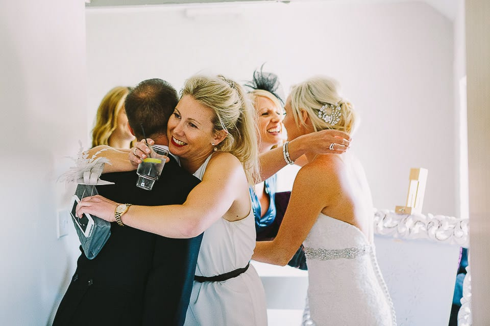 Bride and groom hug guests in the receiving line at Sopley Mill