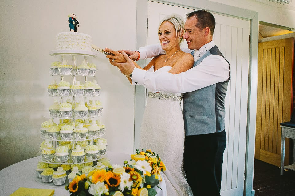 Bride and groom cutting their wedding cake at Sopley Mill