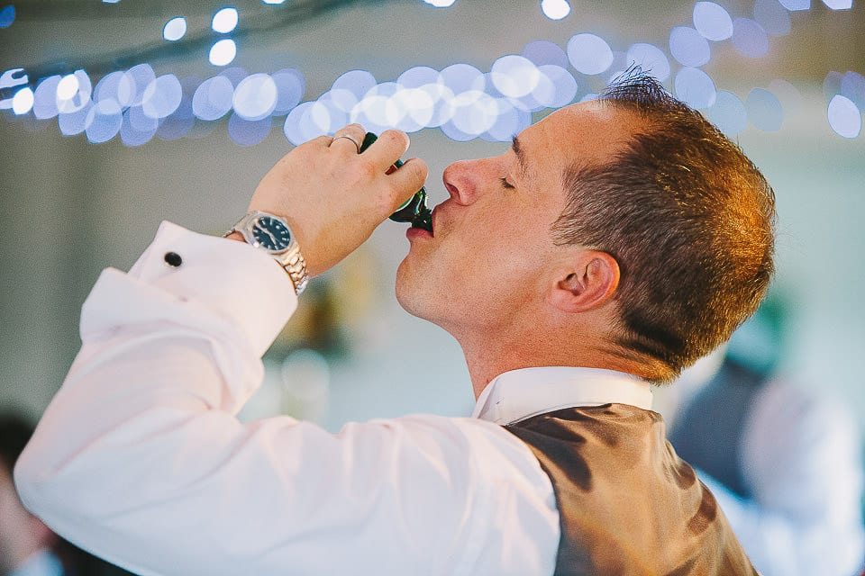 Groom drinking a shot during speeches at Sopley Mill