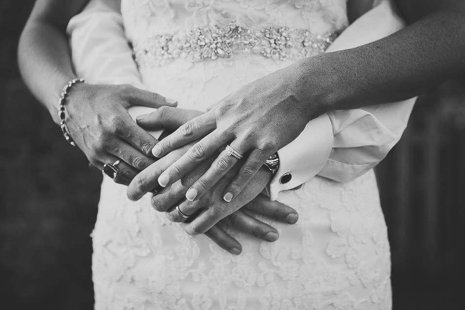 Black and white close up of bride and grooms hands with their wedding rings on