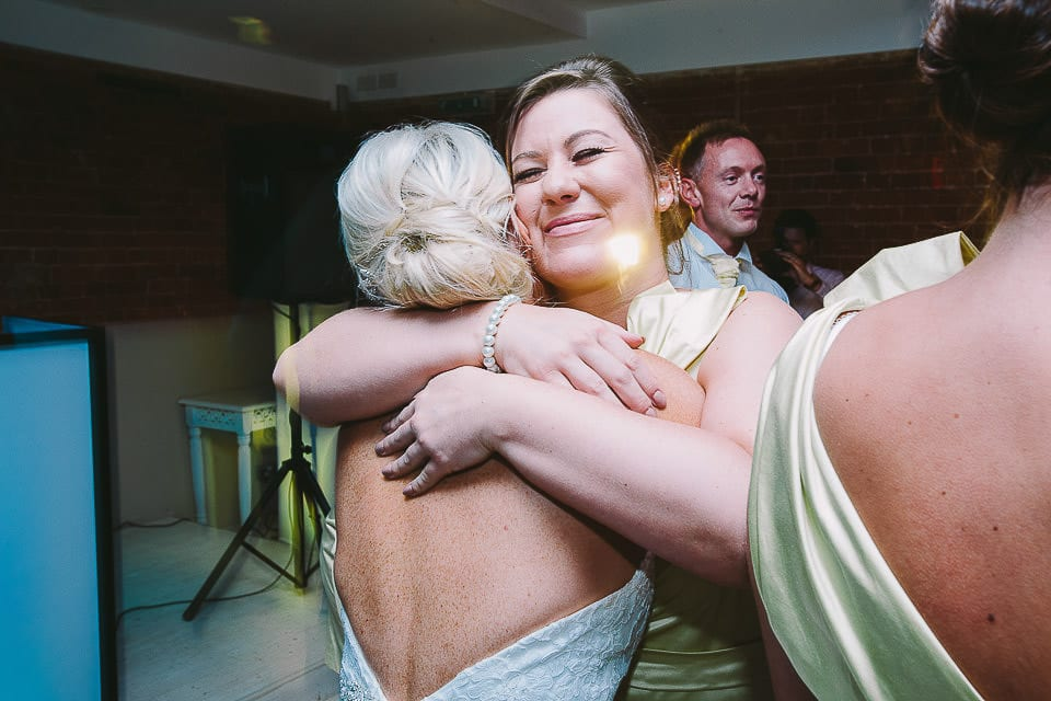 Bridesmaid hugging the bride on the dance floor at Sopley Mill