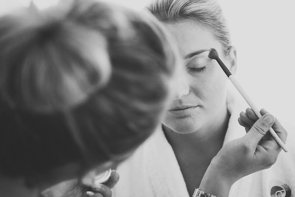 Black and white close up of bridesmaid having her make up applied at The Captains Club Hotel