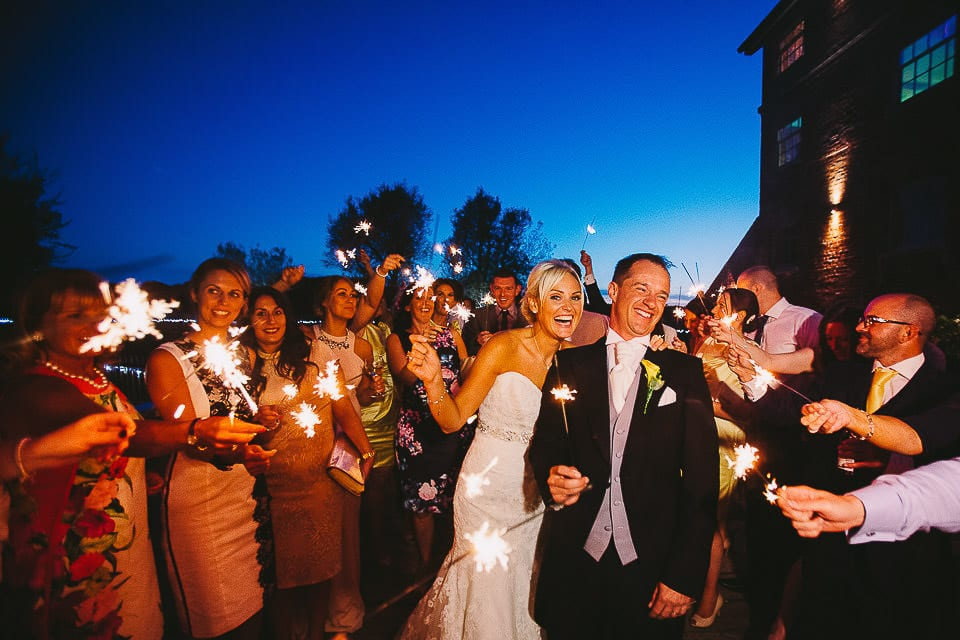 Bride and groom light sparklers on the bridge with some guests at Sopley Mill
