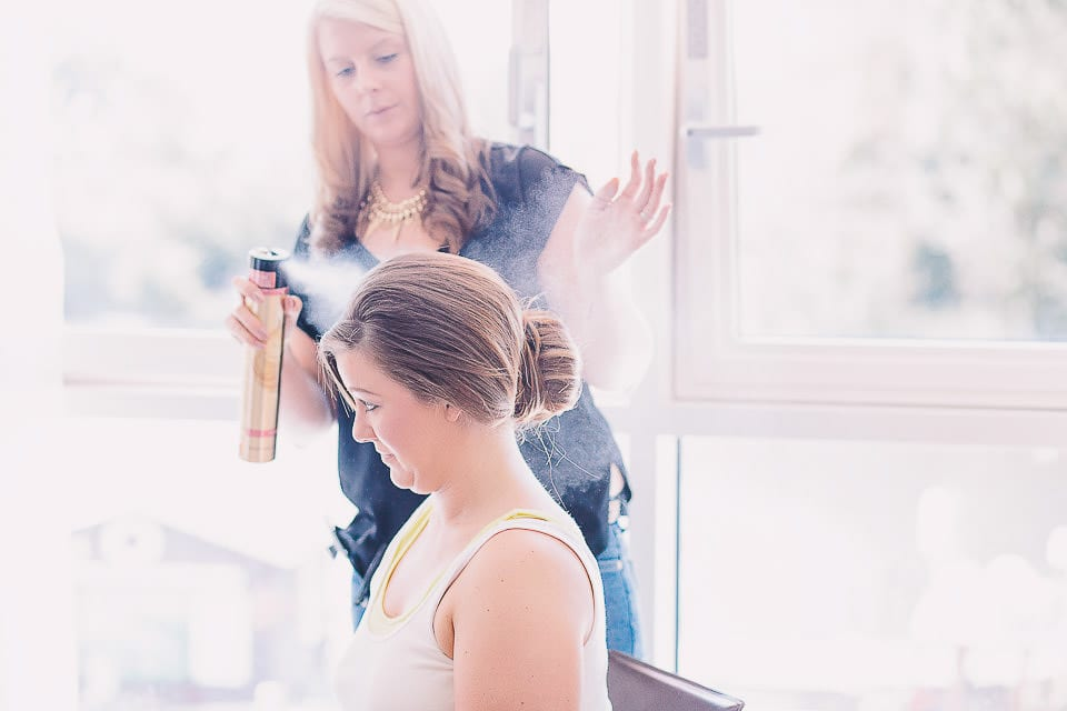 Bridesmaid being sprayed with hairspray at The Captains Club Hotel
