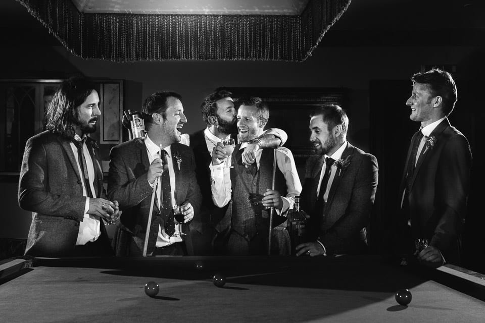 Black and white image of groom and his groomsmen around snooker table