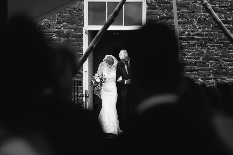 Black and white image of bride and her father walking to ceremony