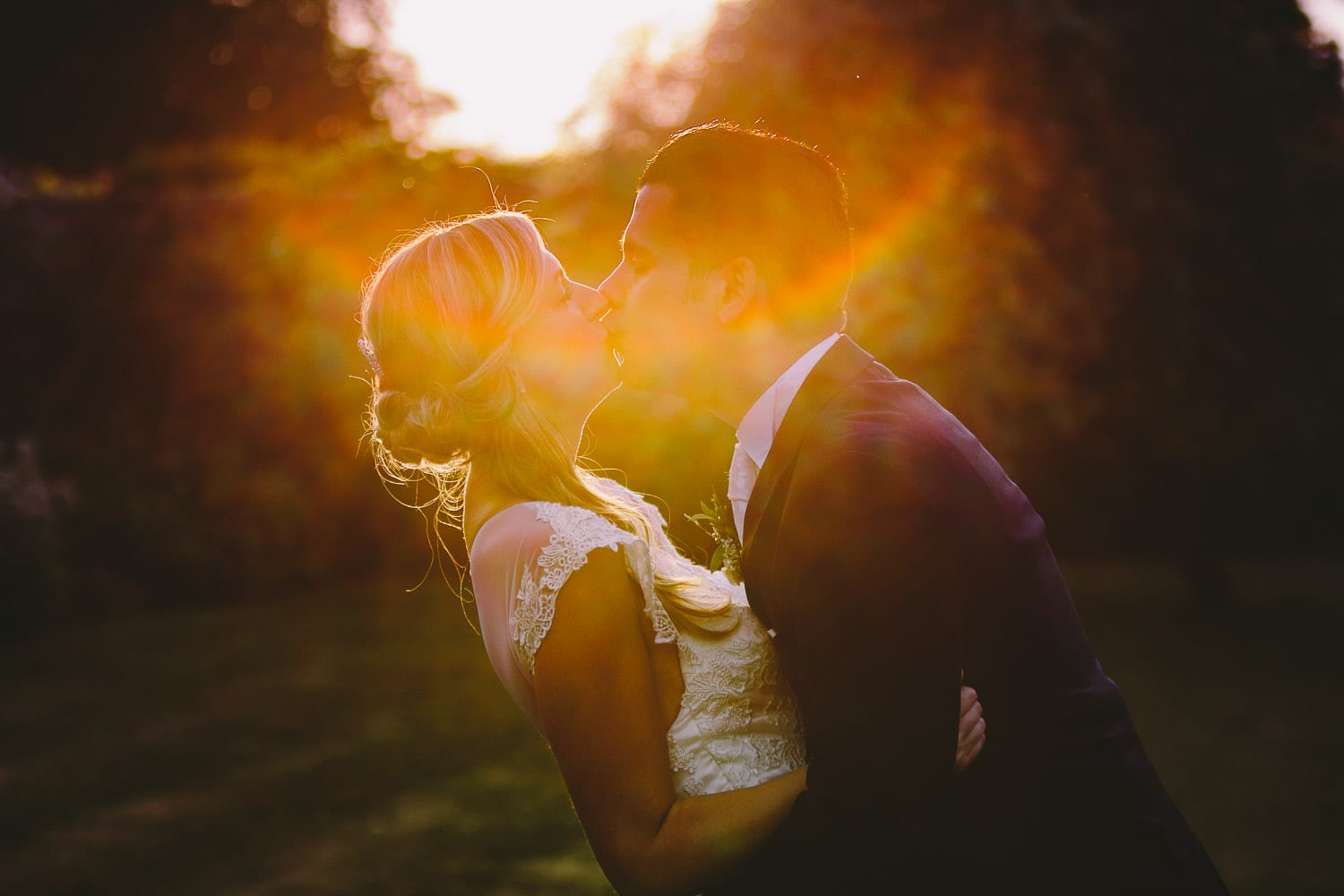 The bride and groom kiss in the sunset