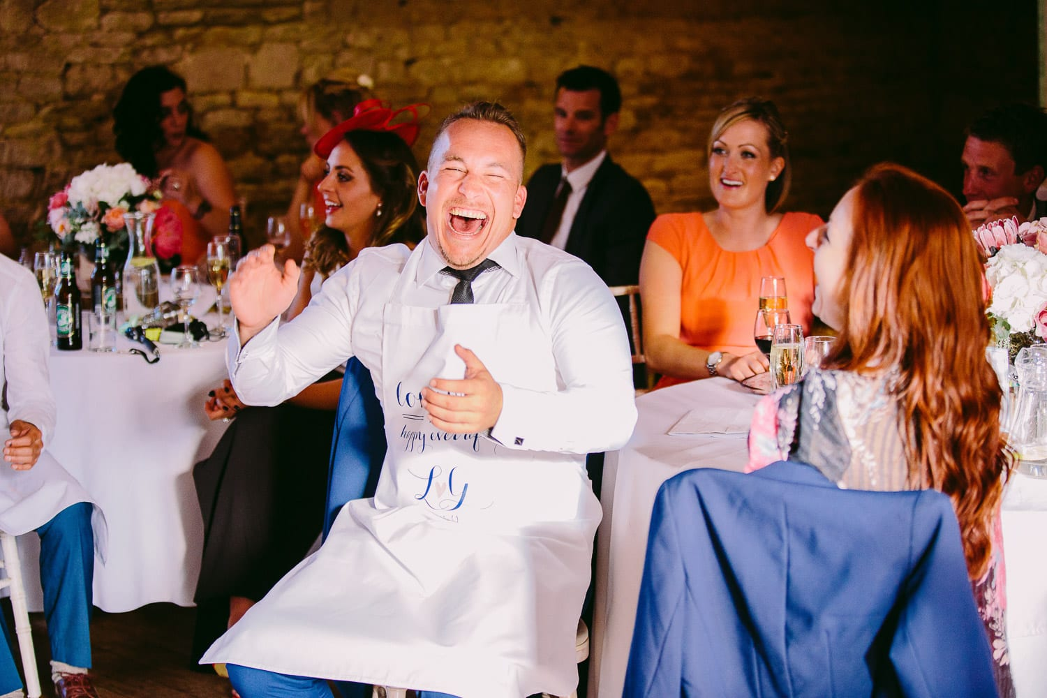 A wedding guest laughing during the speeches