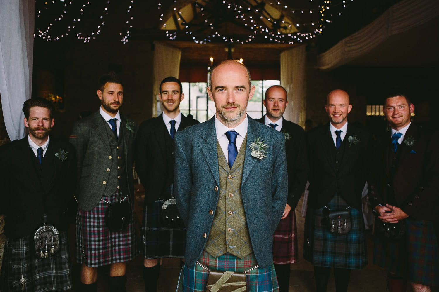 A groom and the ushers lined up in their kilts