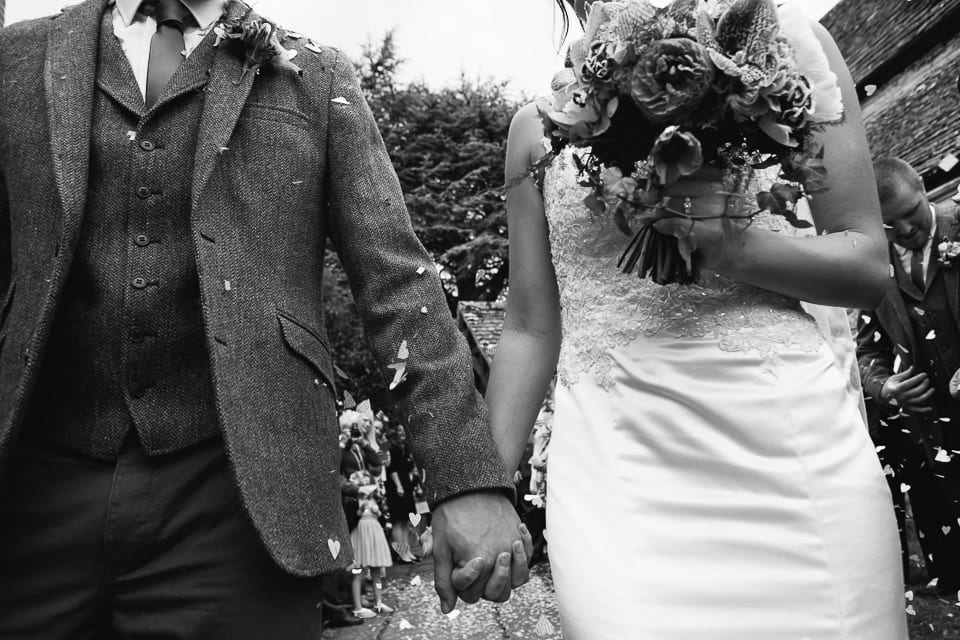 Black and white close up of bride and groom holding hands