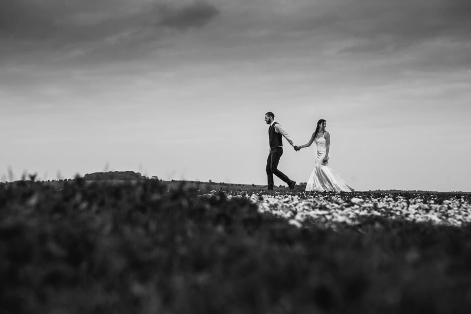 Black and white image of bride and groom walking across field