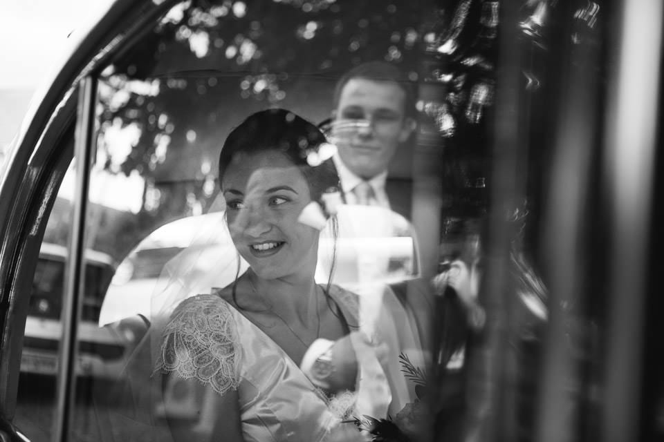 Black and white image of bride in wedding car