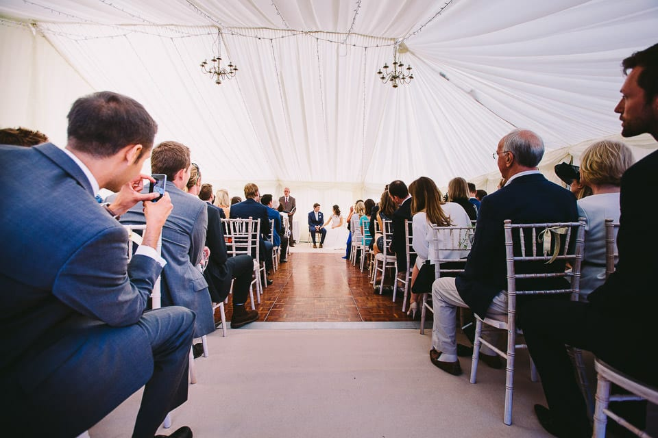 Wide angle of bride and groom sitting during ceremony