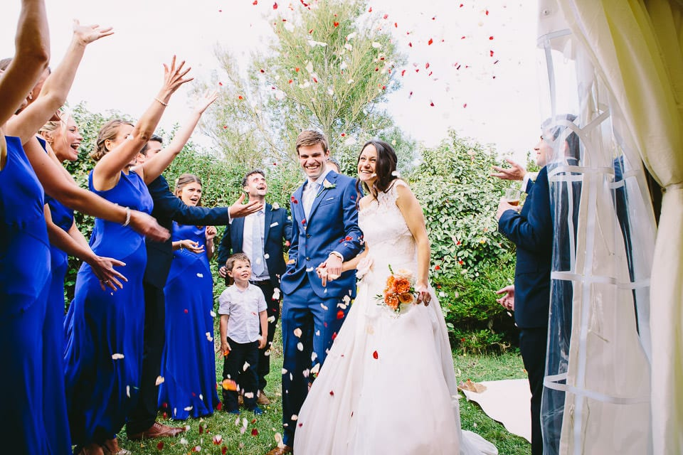 Bride and groom getting surprise confetti shower during entrance to wedding breakfast