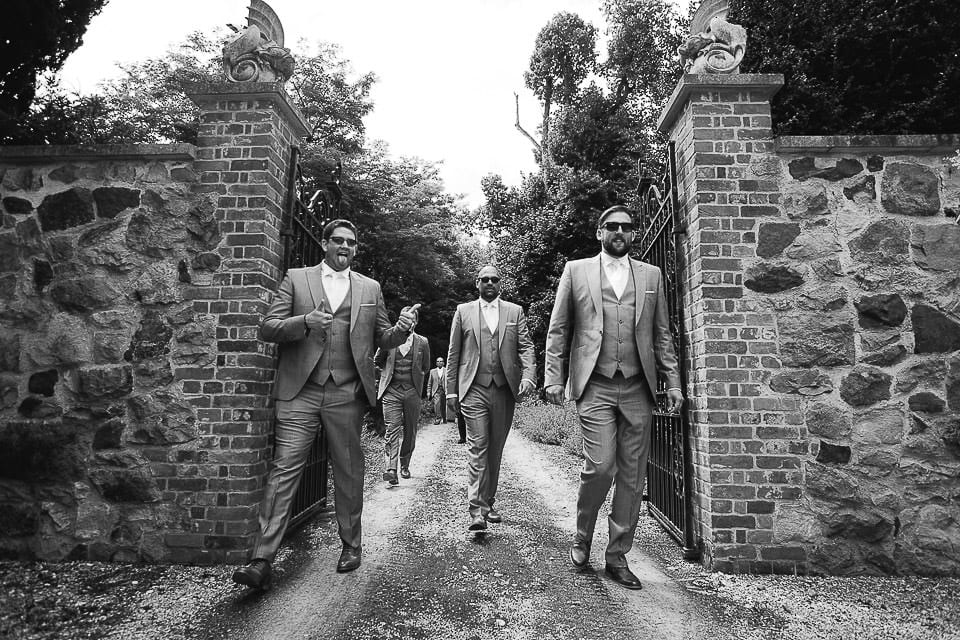Black and white image of groomsmen arriving at Rockley Manor
