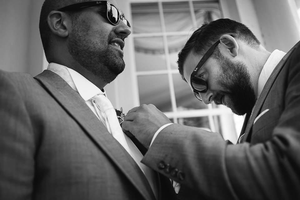 Black and white image of best man putting buttonhole on groomsman