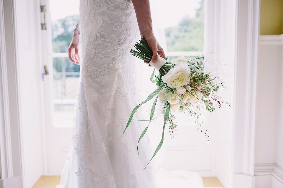 Close up of bride holding her bouquet down at her side