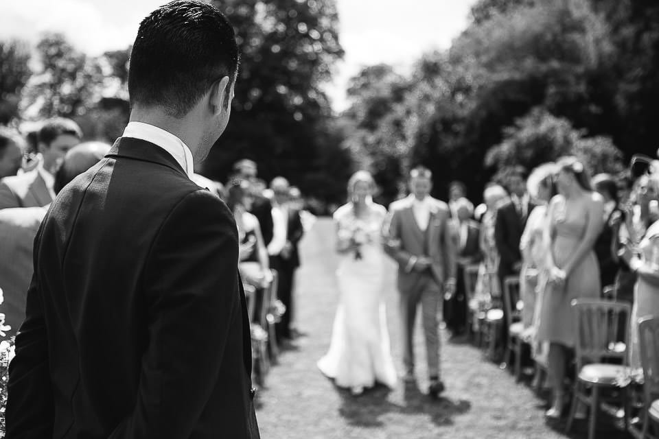 Black and white image of groom watching brides entrance