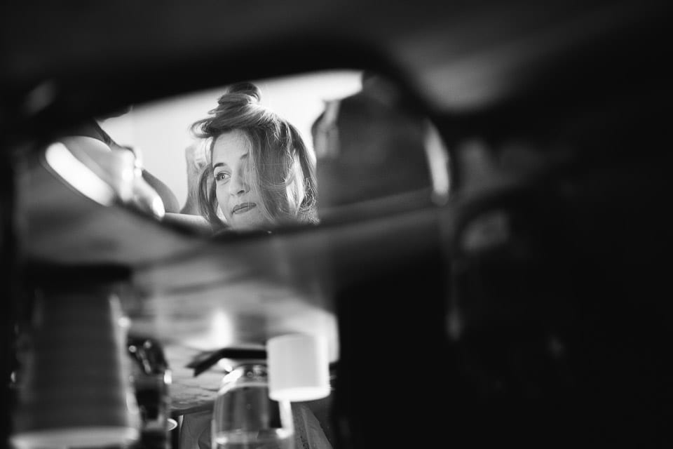 Black and white image of brides reflection in hand mirror