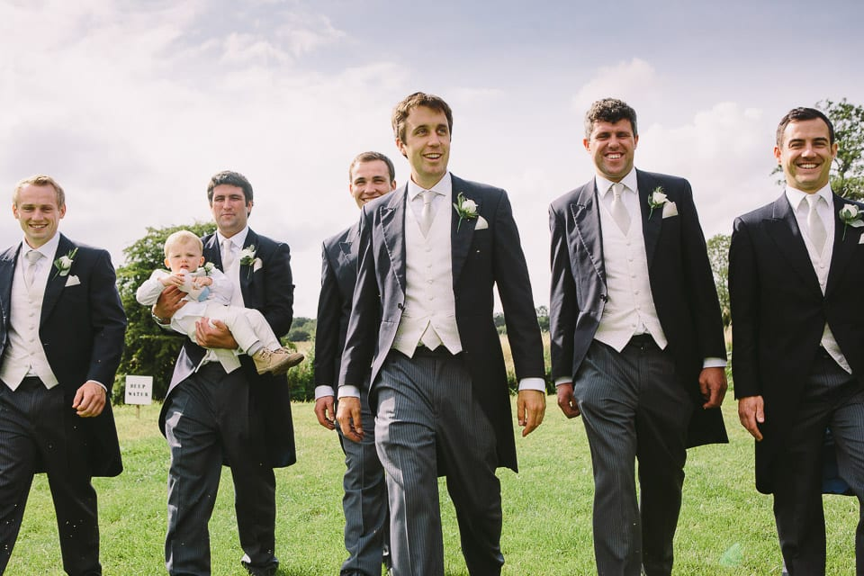 Groom and his groomsmen walking across field with pageboy