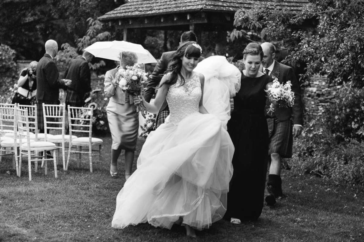 Black and white image of bride and bridesmaid hurrying inside due to rain