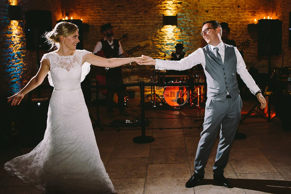 Bride and groom having their first dance in the stone barn