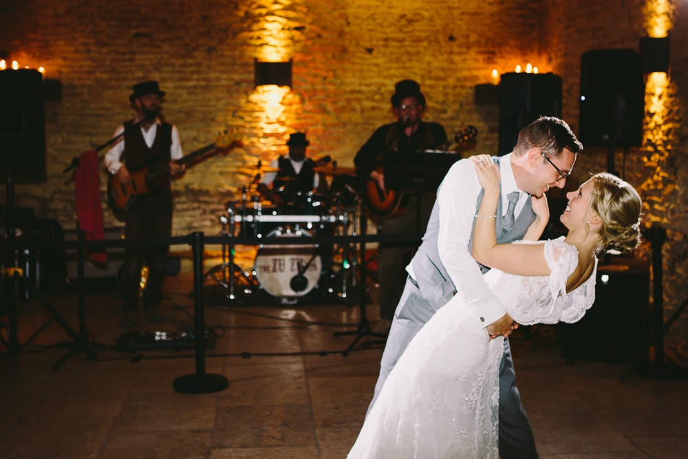 Groom dips his bride during their first dance in the stone barn