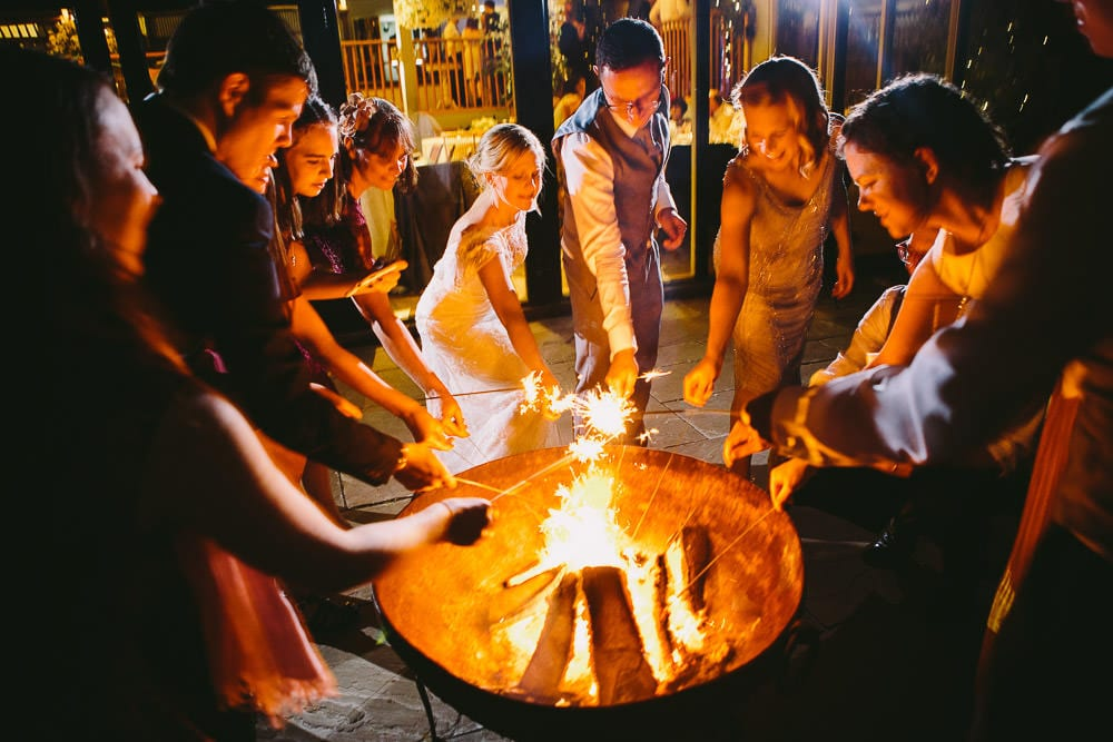 Guests lighting sparklers and toasting marshmallows in the fire pit outside Cripps Stone Barn