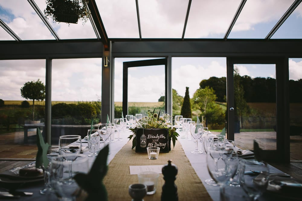 Dutch barn set up for the wedding breakfast with view of fields through large windows at Cripps Stone Barn