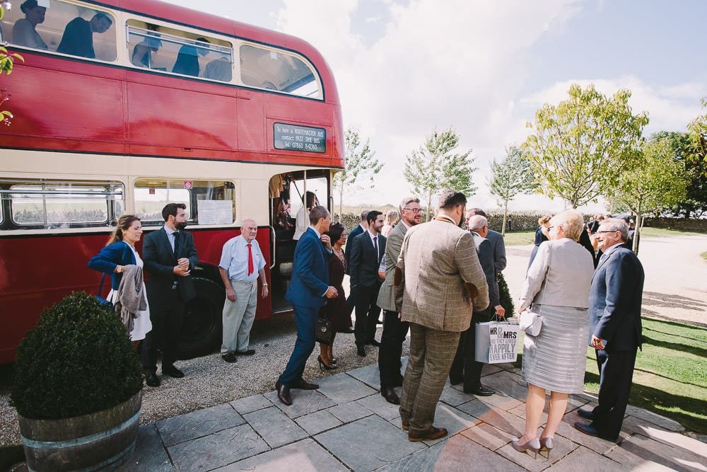 Wedding guests departing the vintage routemaster bus for the wedding at Cripps Stone Barn
