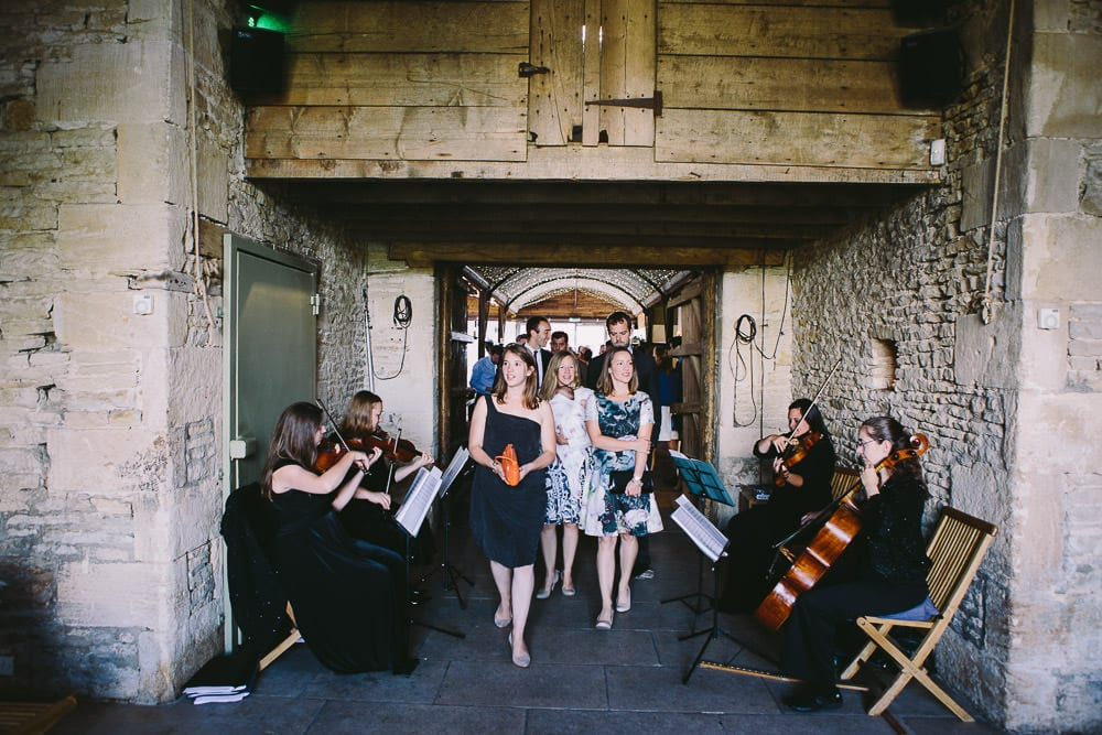 String quartet and guests arriving into the barn for the wedding at Cripps Stone Barn