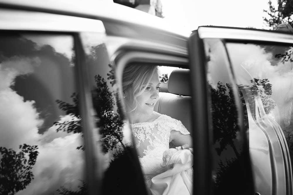Black and white image of bride in wedding car at Cripps Stone Barn