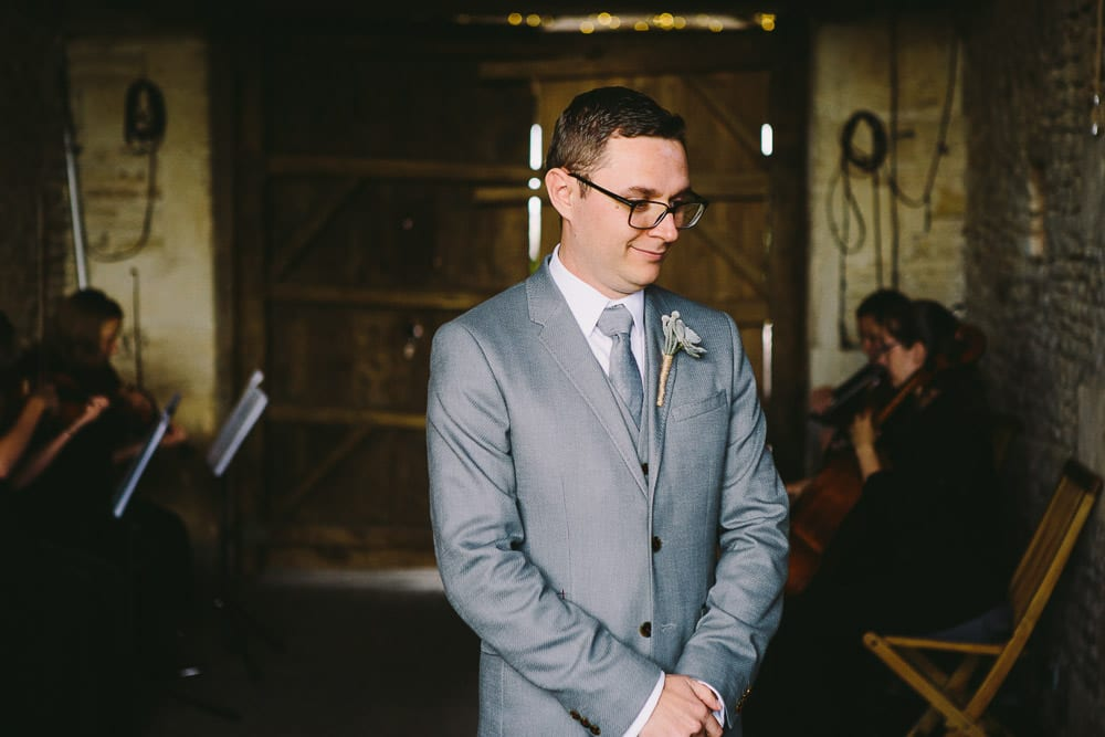 Groom awaiting the arrival of his bride and her father at Cripps Stone Barn